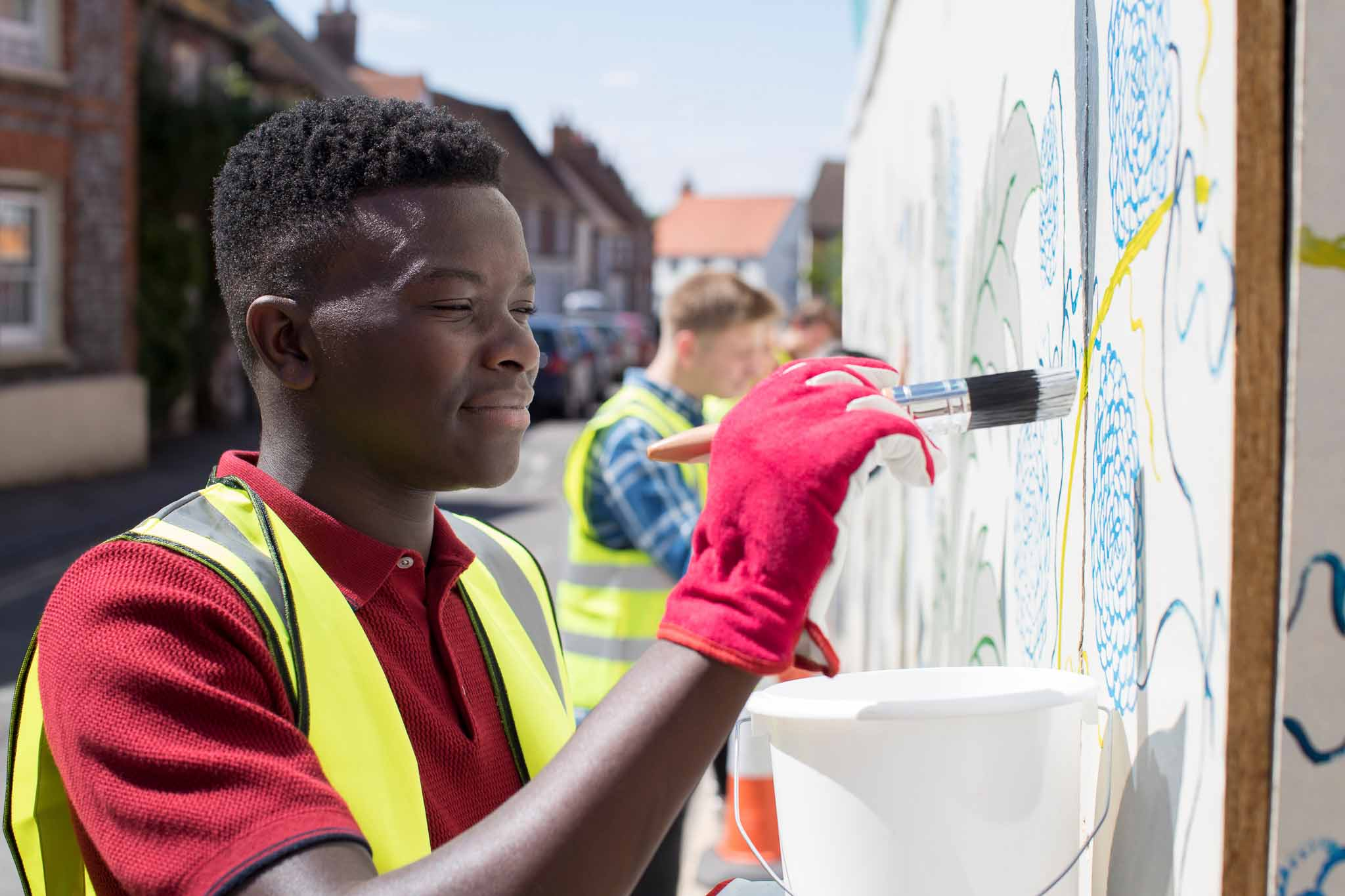 Teenagers paint a colorful mural on a sunny street, and have all the tools and gear to do the job perfectly.