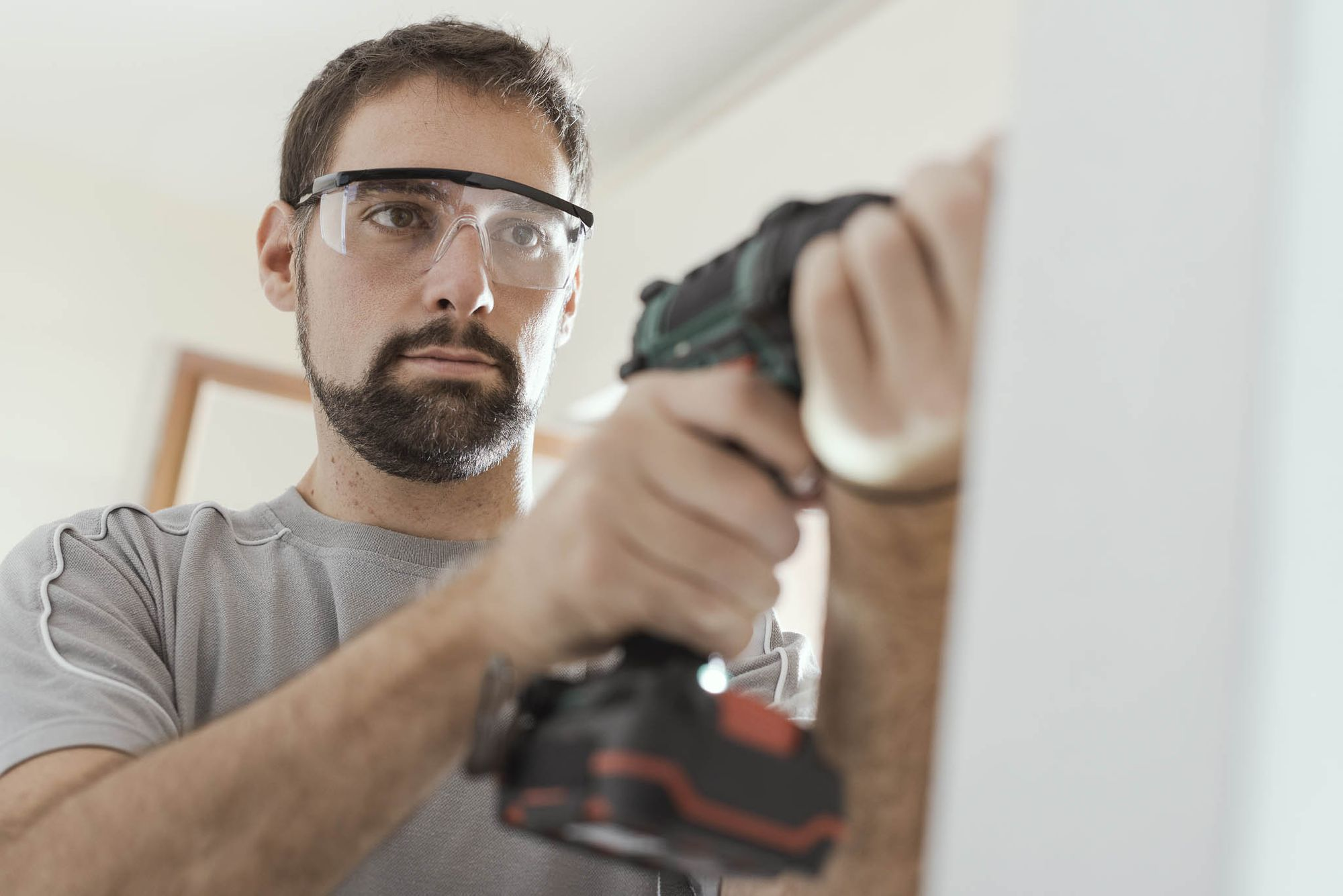 A man wearing protective goggles happily uses an electric drill to make the holes necessary to install a tablet mount.