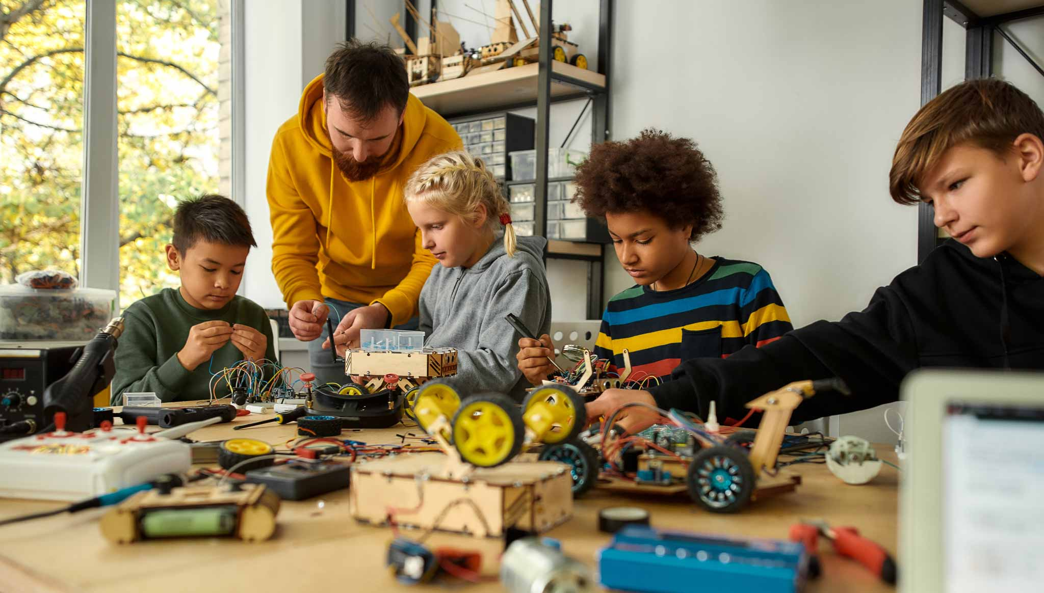 Four children and an adult sit around a colorful table table full of small vehicle components. Some use tools, other are working with adhesives to make small robots.