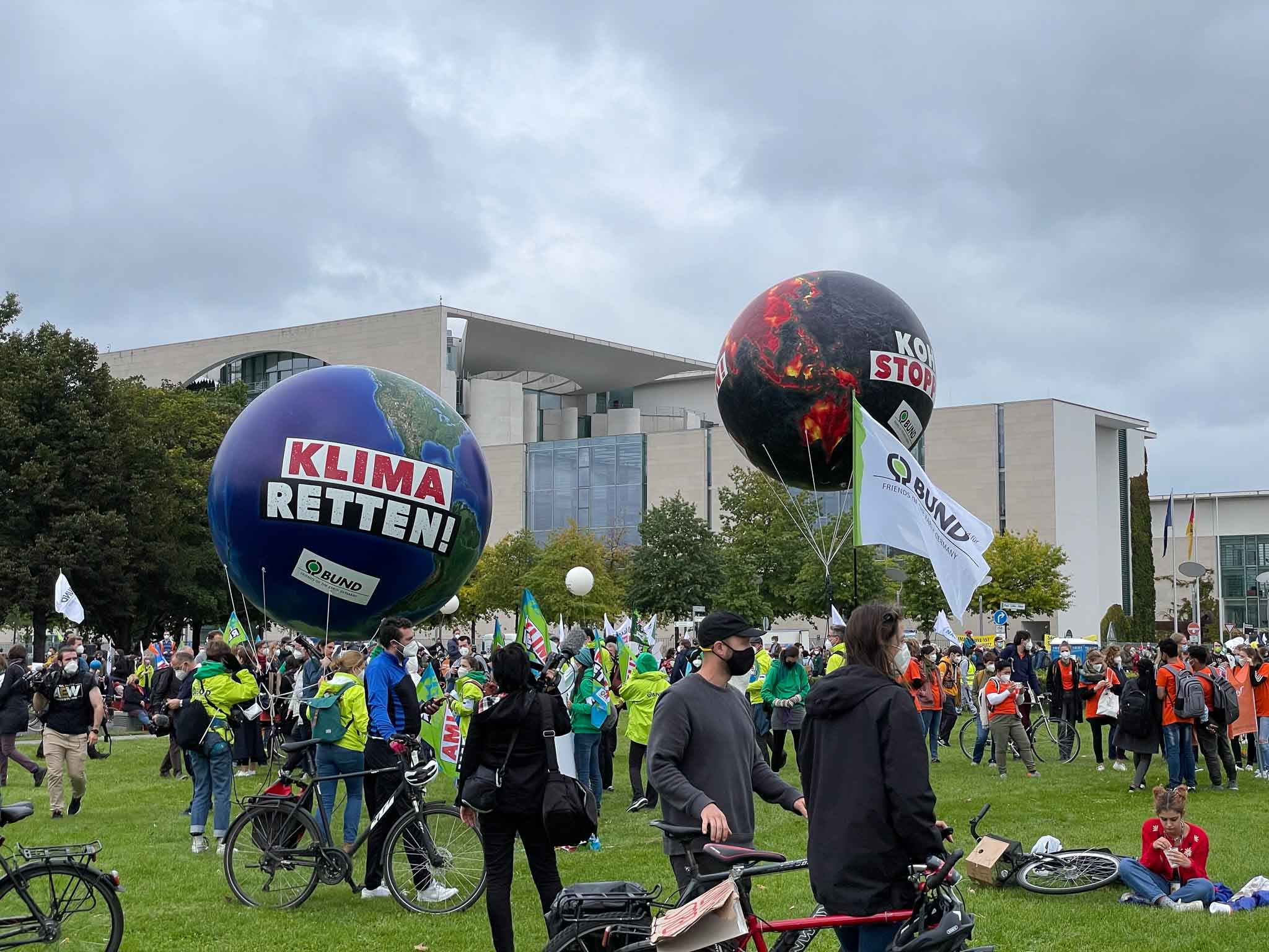 """Berliners—including members of the Cobot team—gather in the grass front of the German parliament with their bicycles, placards, and balloons that say """"Klima Retten!"""""""